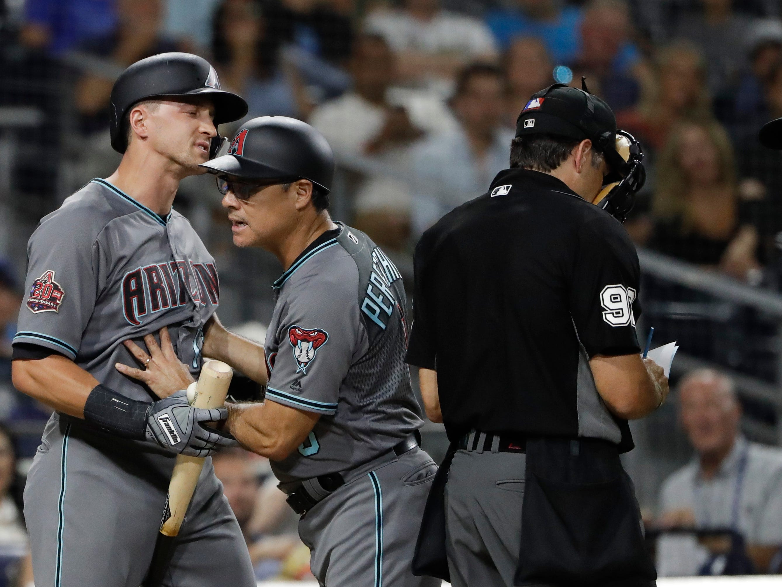 Arizona Diamondbacks' Nick Ahmed, left, is held back by third base coach Tony Perezchica, center, as he argues with umpire James Hoye during the third inning of a baseball game against the San Diego Padres Friday, Aug. 17, 2018, in San Diego.
