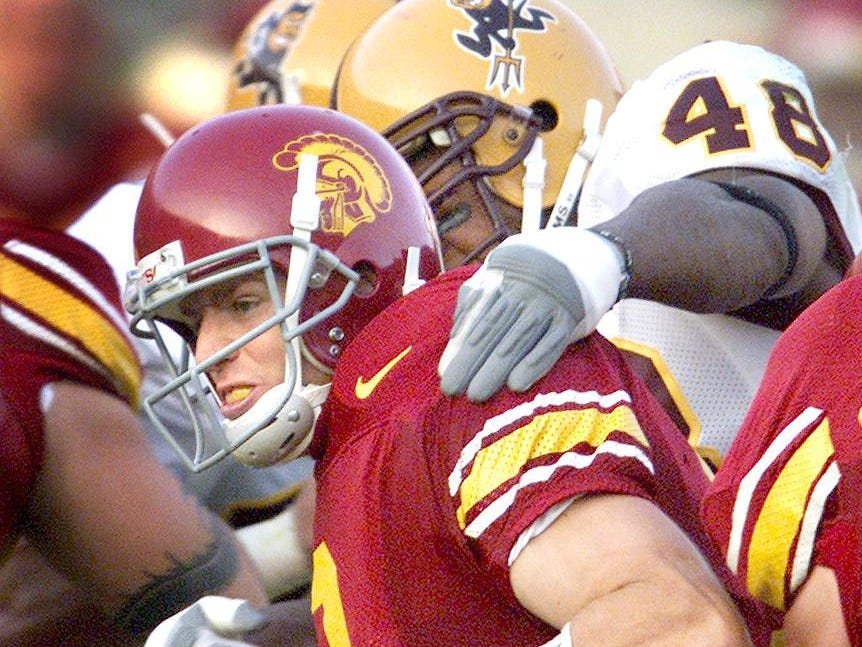 ASU defensive end Terrell Suggs wraps up USC quarterback Carson Palmer for a sack in the second half of game action between the two teams, at the Coliseum, in Los Angeles, CA, on Oct. 13, 2001. Photo by