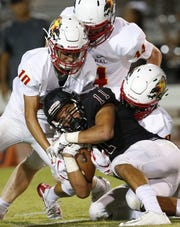 Hamilton Mo Parson (11) is stopped by Chaparral Ben Eddleblute (10) and Parker Smith (44) and Deavon Crawford (9), right,  during a high school football game at Hamilton in Chandler on August 17, 2018. #hsfb