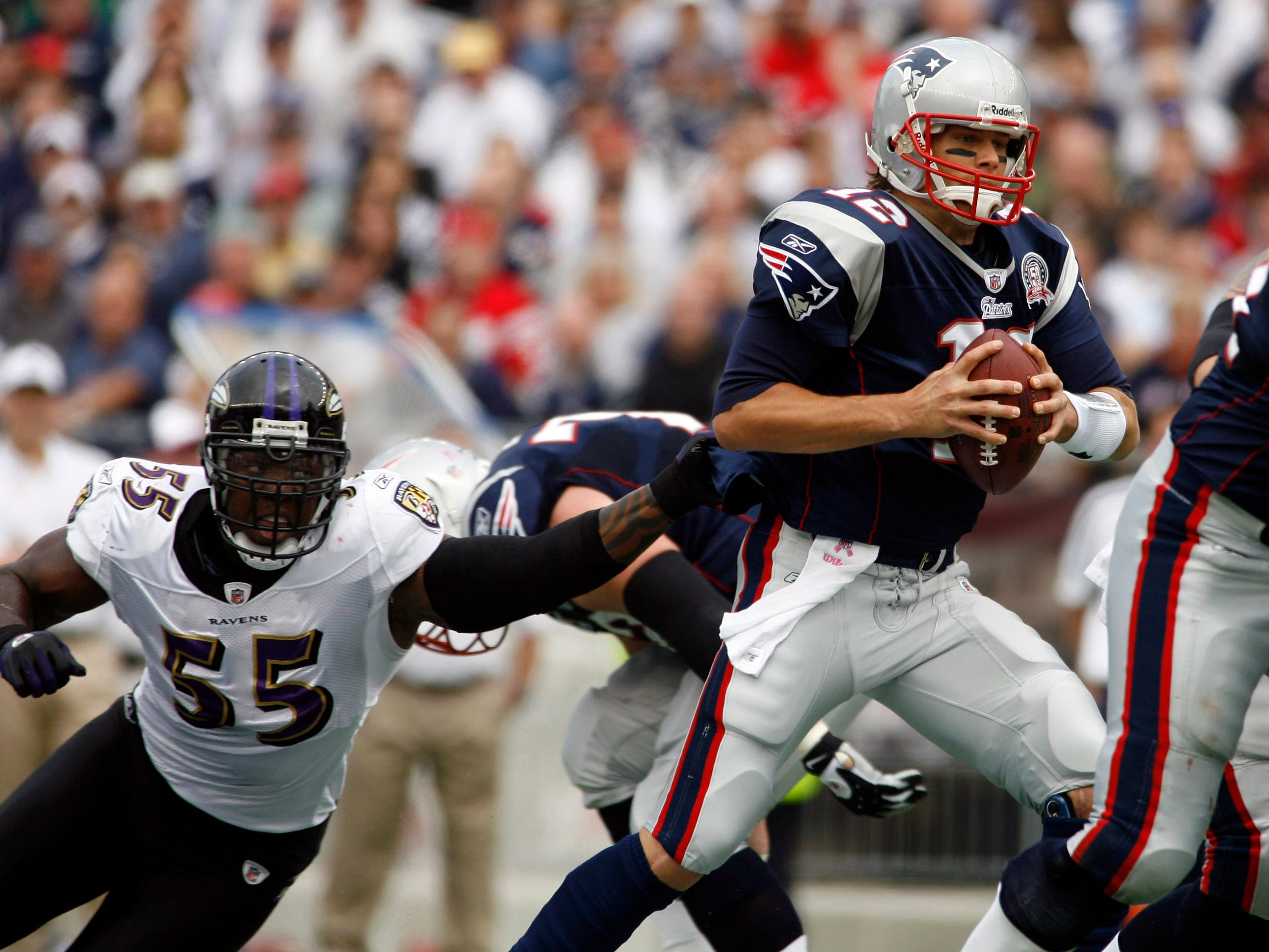 New England Patriots quarterback Tom Brady (12) escapes a sack attempt by Baltimore Ravens linebacker Terrell Suggs (55) during the first half at Gillette Stadium.
