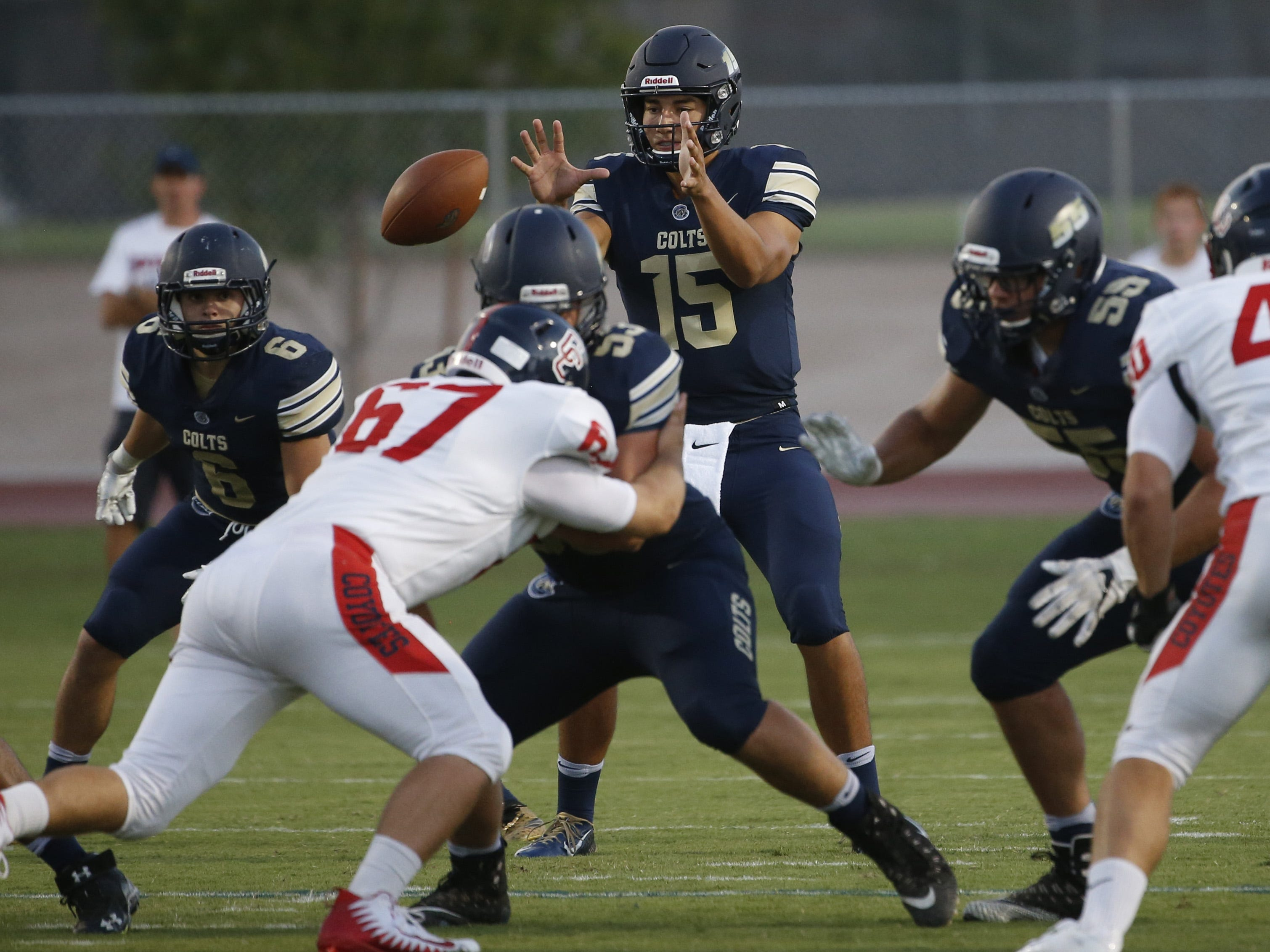 Casteel's Gunner Cruz (15) takes the snap against Centennial during the first half at Casteel High School in Queen Creek, Ariz. on Aug. 17, 2018.