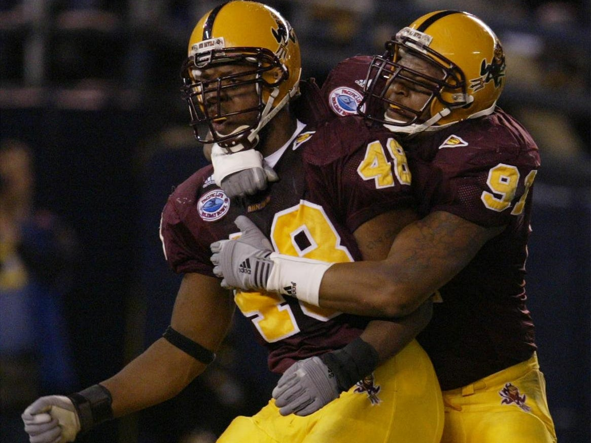 ASU's Terrell Suggs is hugged by teammate Jimmy Verdon (right) after Suggs sacks Kansas State QB Ell Roberson during first half action at the Holiday Bowl in San Diego, CA.