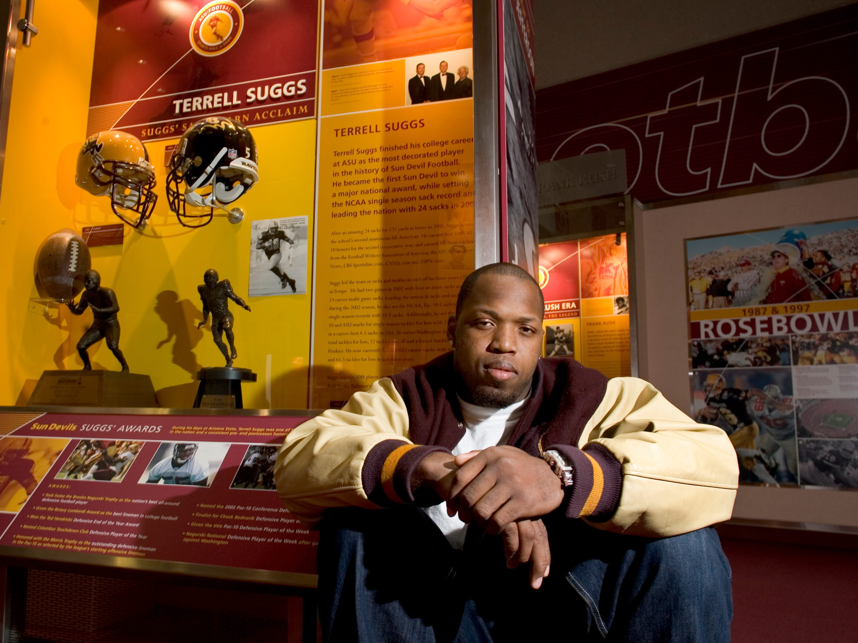 Portrait of Terrell Suggs in front of his display at the ASU Athletic Hall of Fame.