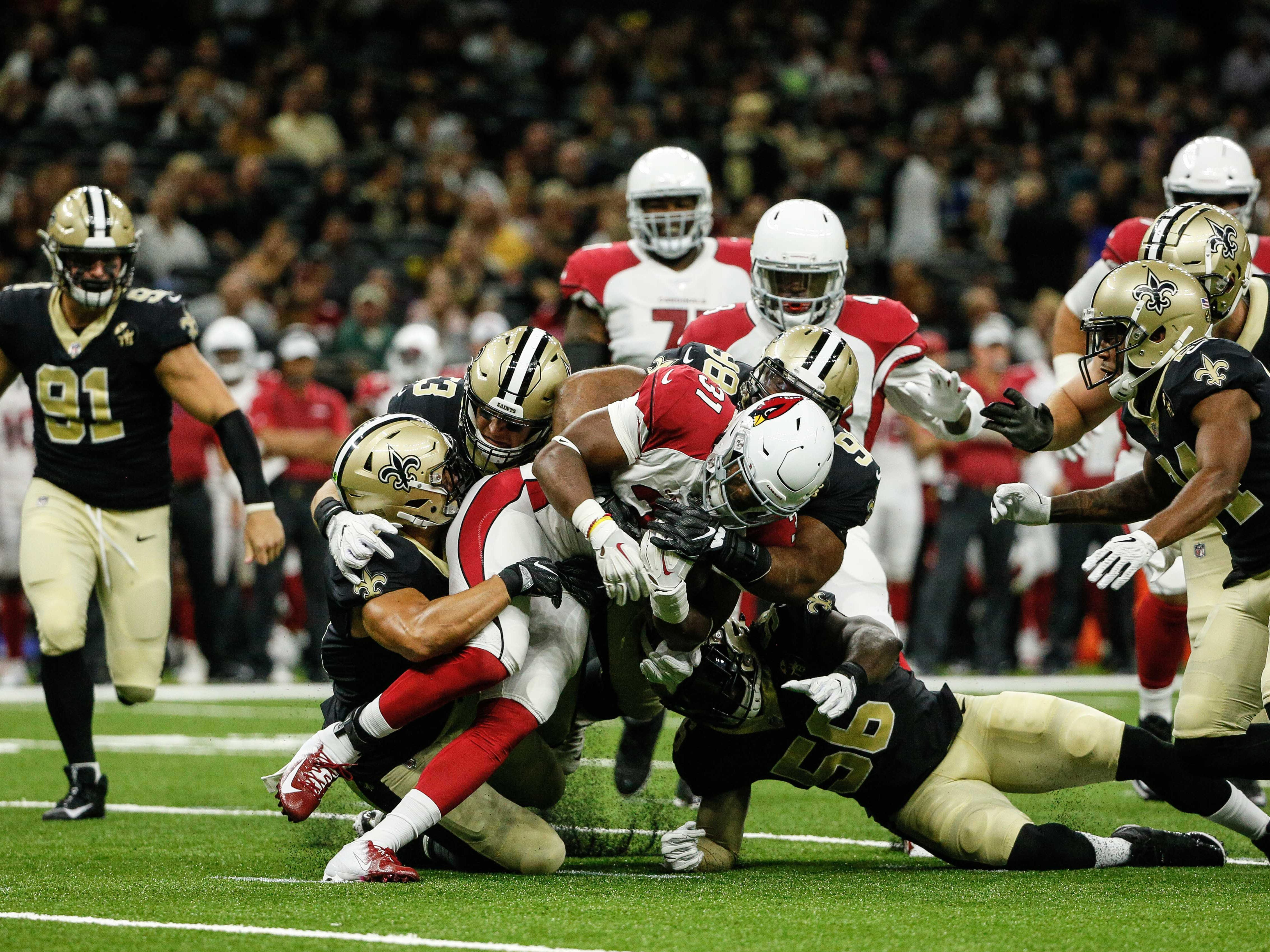 Aug 17, 2018: Arizona Cardinals running back David Johnson (31) is tackled by a group of New Orleans Saints defenders during the first half of a preseason game at the Mercedes-Benz Superdome.