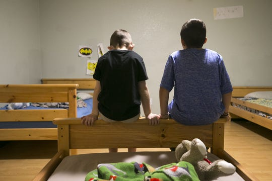 A second-grader (left) and a third-grader who are in the Arizona foster-care system sit on the edge of a bed in the sleeping area at the Child Crisis Arizona shelter in Mesa on Feb. 20, 2018.