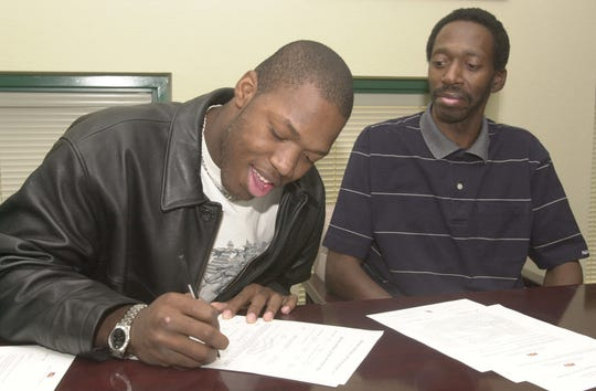 Terrell Suggs of Hamilton High School in Chandler signs a letter of intent to attend ASU while his father Donald Suggs looks on Feb. 2, 2000.