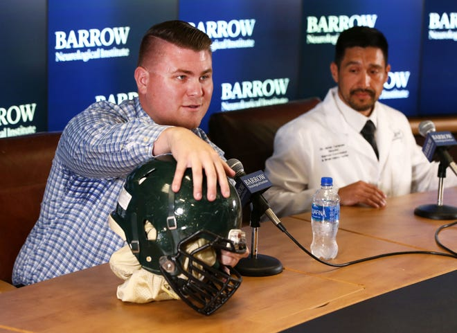 Former Basha High defensive lineman Wyatt Ellis (left) shows his damaged helmet while discussing concussions in high school sports on Aug. 17, 2018. Ellis suffered long-term effects from a concussion that ended his football career.