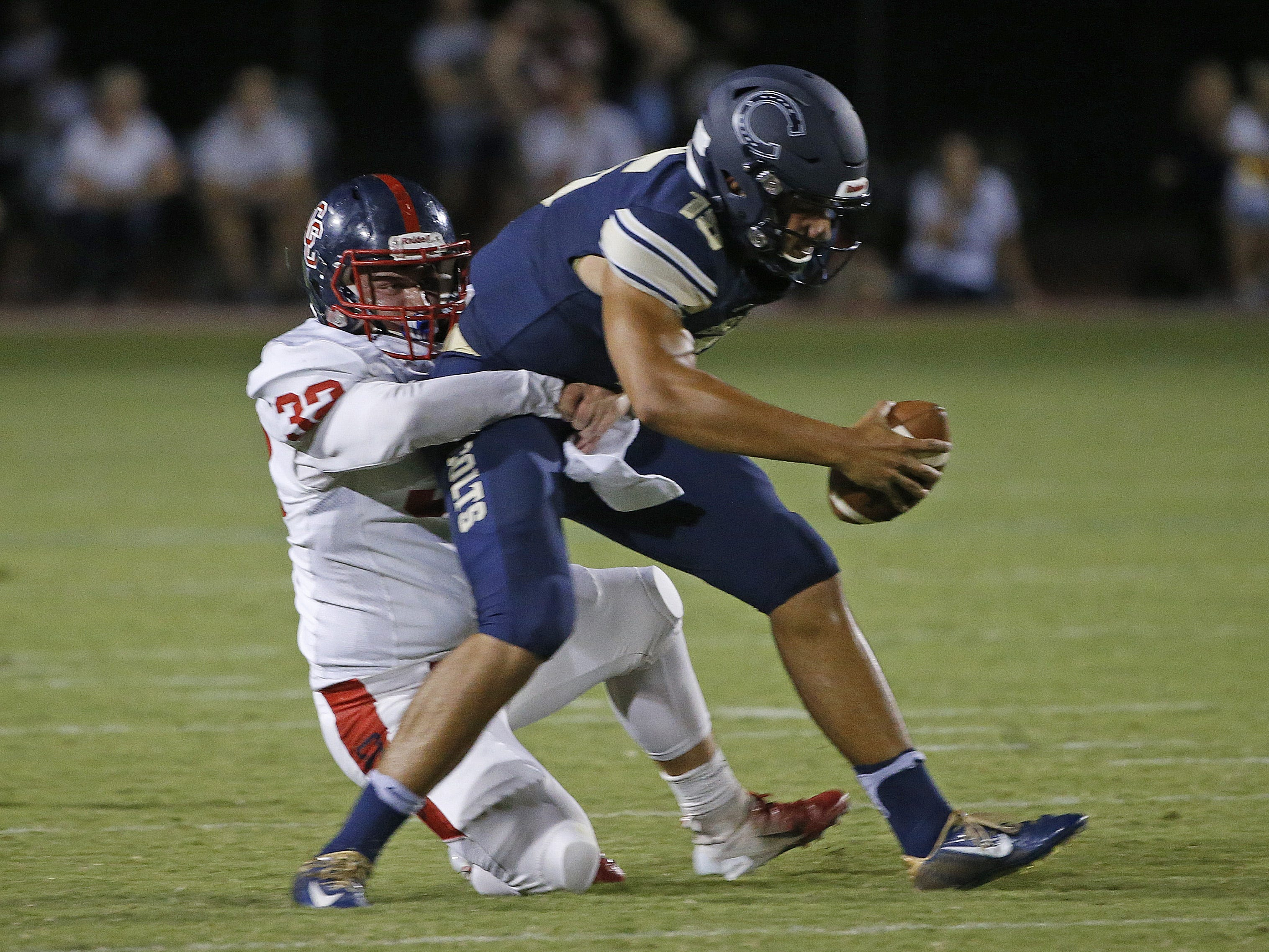 Centennial's Connor Knudsen (32) sacks Casteel's Gunner Cruz (15) during the first half at Casteel High School in Queen Creek, Ariz. on Aug. 17, 2018.