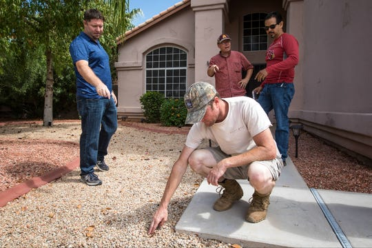 Meteorite hunters Robert Ward (front) and Ruben Garcia (back right) search the spot where the meteorite was found earlier this week for fragments with homeowner Cody Horvath (left) and ASU professor Laurence Garvie (back left).