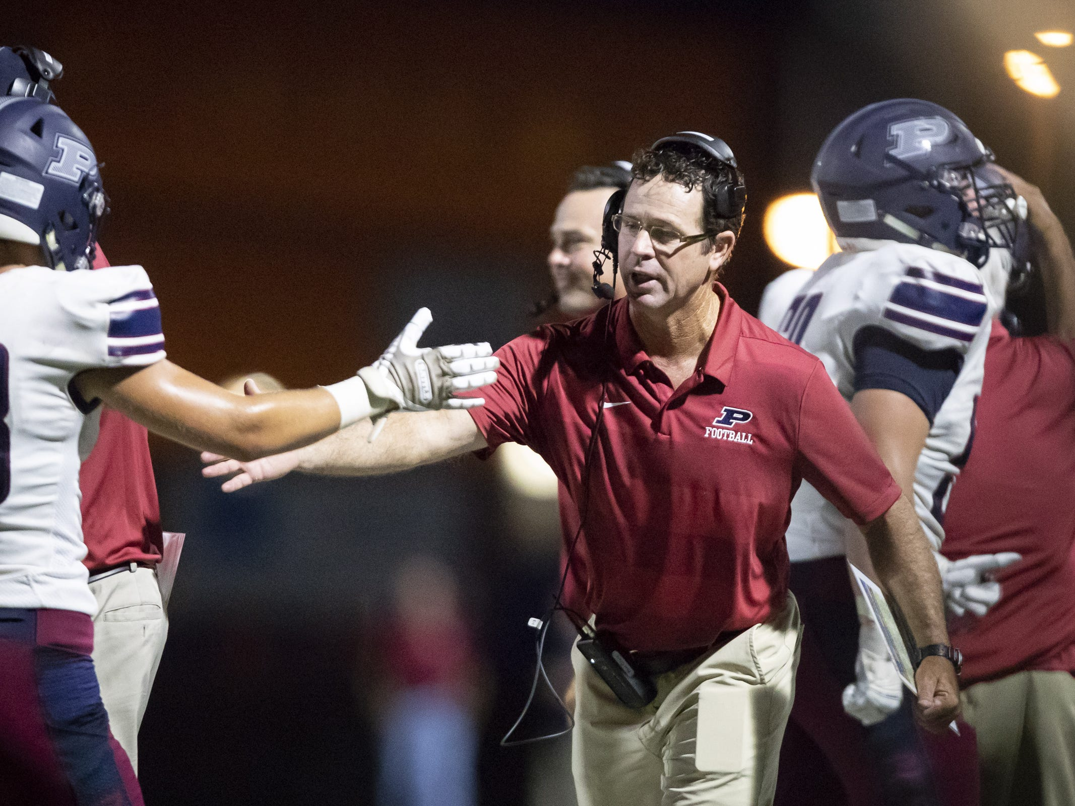 Head coach Preston Jones of the Perry Pumas high-fives wide receiver Connor Boyd (83) during the game against the Pinnacle Pioneers at Pinnacle High School on Friday, August 17, 2018 in Phoenix, Arizona.