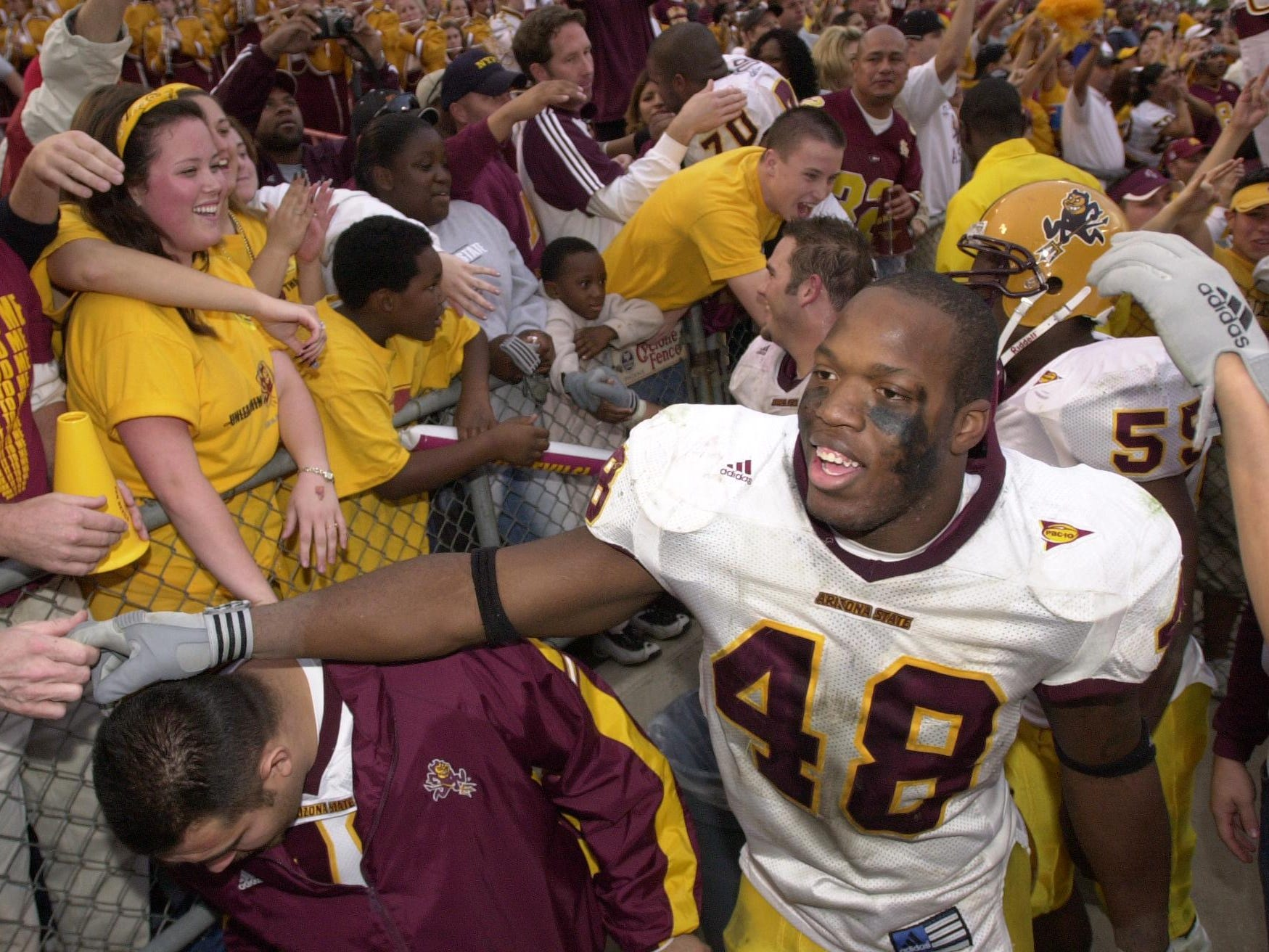 ASU's Terrell Suggs celebrates with the Sun Devils fans after ASU defeated the Wildcats 34-20 in Tucson Nov. 29, 2002.