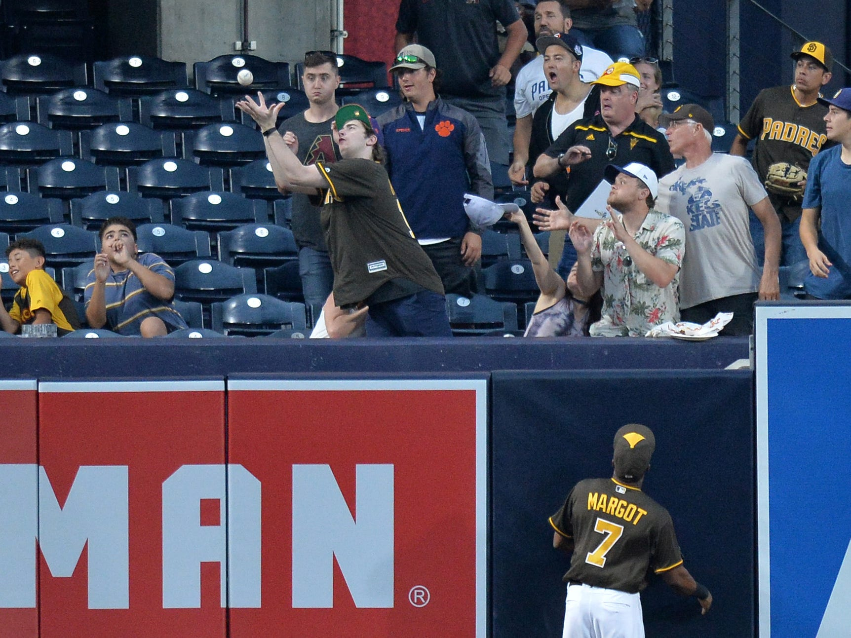 Aug 17, 2018: A San Diego Padres fan tries to catch a two run home run by Arizona Diamondbacks first baseman Paul Goldschmidt (not pictured) during the first inning as center fielder Manuel Margot (7) looks on at Petco Park.
