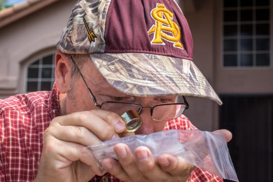 ASU professor Laurence Garvie examines the plastic-bag encased meteorite and fragments that fell in the front yard of Cody Horvath's north Glendale home on July 27.
