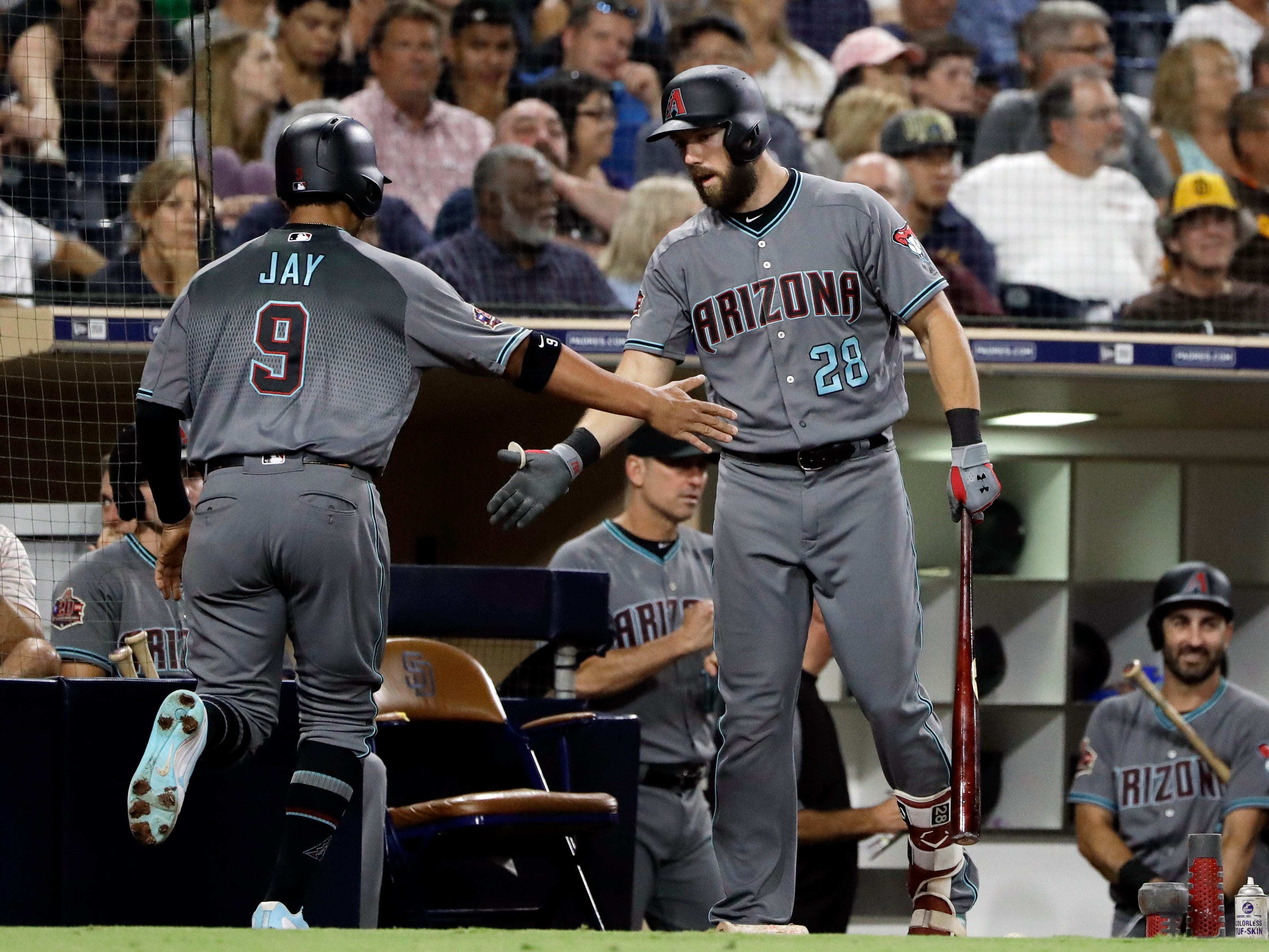 Arizona Diamondbacks' Jon Jay (9) is greeted by Steven Souza Jr. after scoring during the fourth inning of a baseball game against the San Diego Padres on Friday, Aug. 17, 2018, in San Diego.