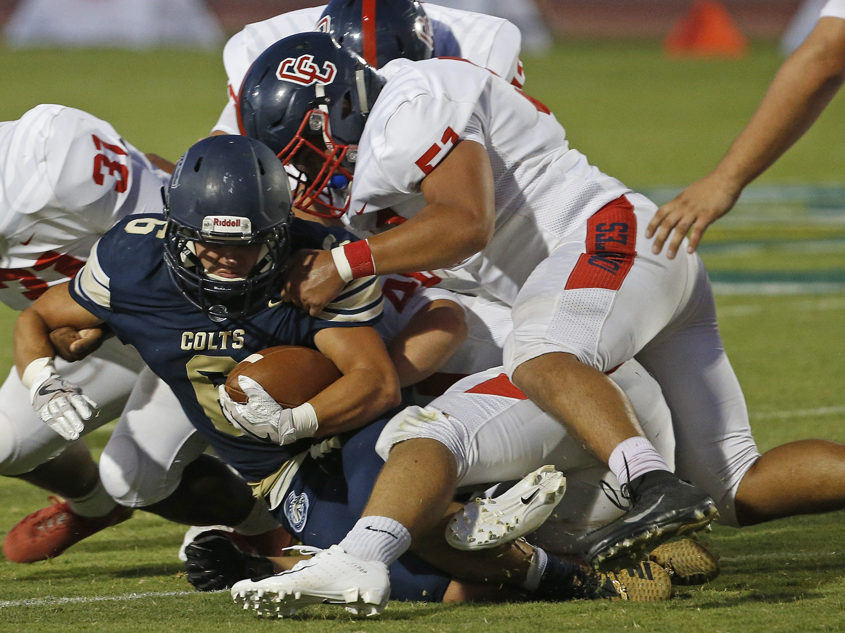 Centennial's Xavier Garcia (51) tackles Casteel's Mack Johnson (6) during the first half at Casteel High School in Queen Creek, Ariz. on Aug. 17, 2018.
