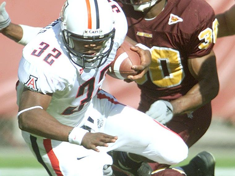 Arizona halfback Clarence Farmer gets tripped up by ASU defensive end Terrell Suggs as teammate Jason Shivers (#30) comes into to help out in 1st half action at Sun Devil Stadium on Nov. 23, 2001.