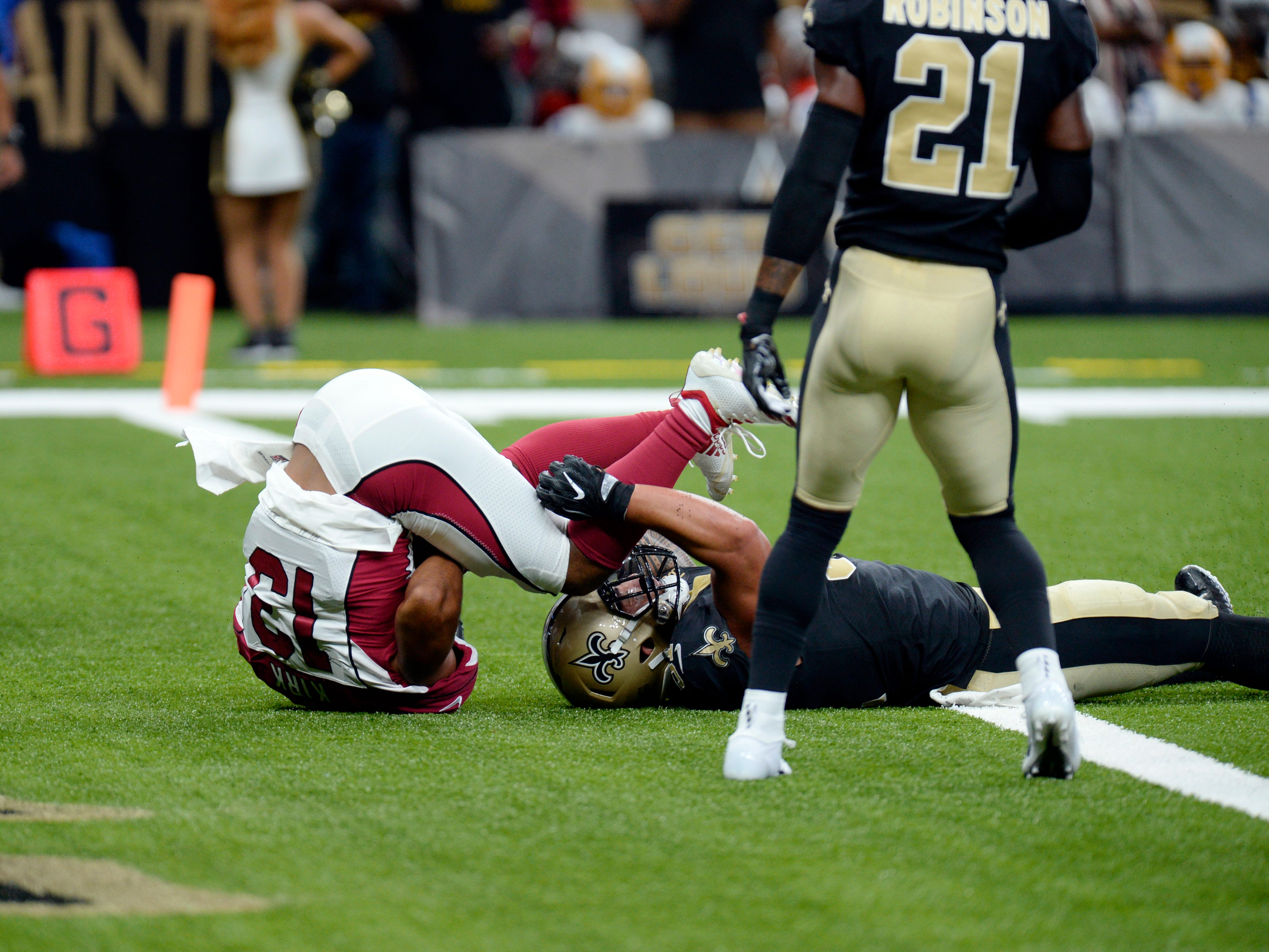 Arizona Cardinals wide receiver Christian Kirk (13) pulls in a touchdown reception as New Orleans Saints linebacker Manti Te'o covers in the first half of an NFL preseason football game in New Orleans, Friday, Aug. 17, 2018.