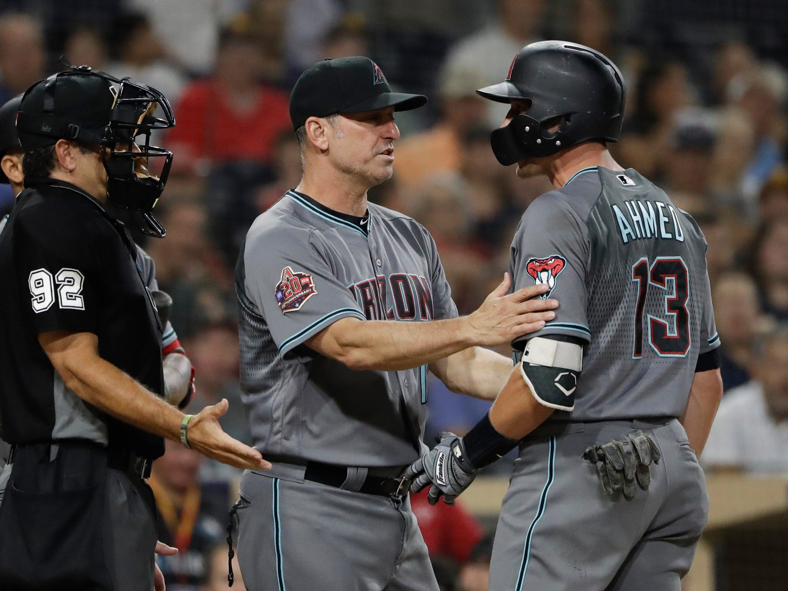 Arizona Diamondbacks' Nick Ahmed, right, is held back by manager Torey Lovullo, center, as he argues with umpire James Hoye during the third inning of a baseball game against the San Diego Padres Friday, Aug. 17, 2018, in San Diego.