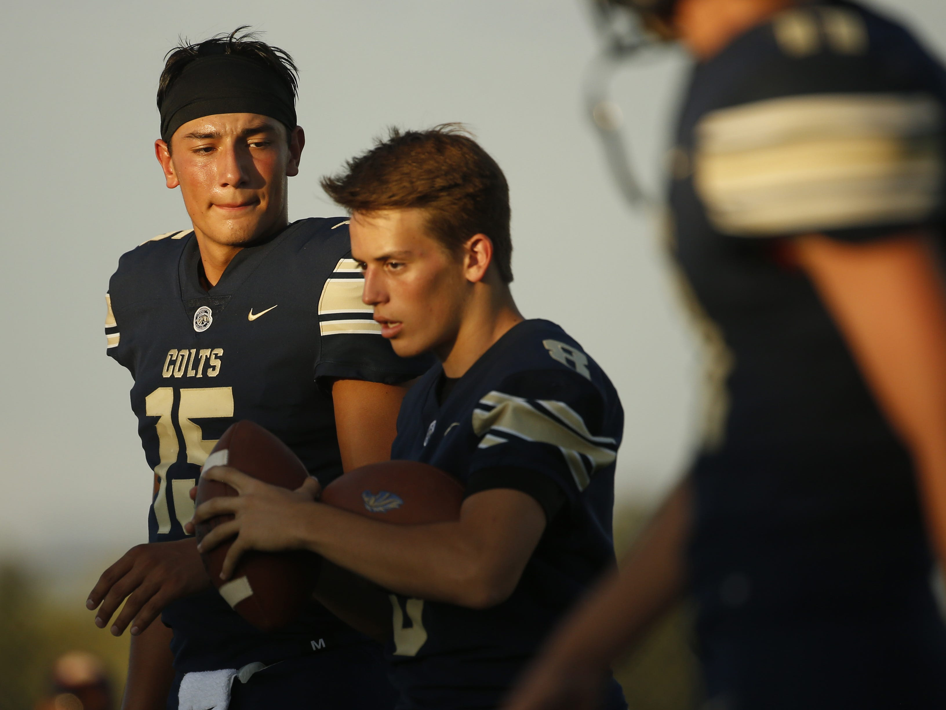 Casteel's quarterback Gunnar Cruz (15) warms up with teammates before a game against Centennial at Casteel High School in Queen Creek, Ariz. on Aug. 17, 2018.