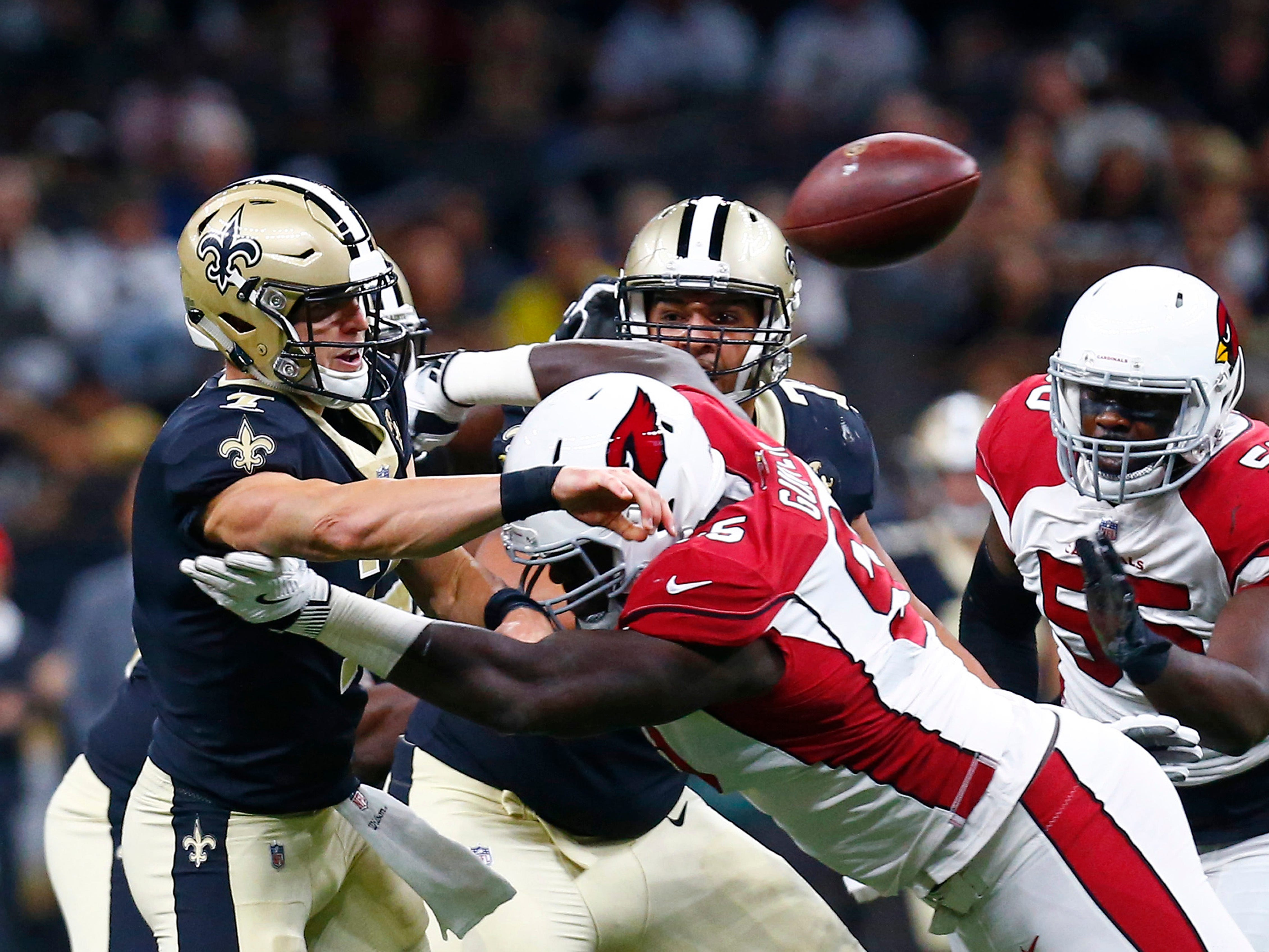 New Orleans Saints quarterback Taysom Hill (7) passes under pressure from Arizona Cardinals defensive tackle Rodney Gunter in the first half of an NFL preseason football game in New Orleans, Friday, Aug. 17, 2018.