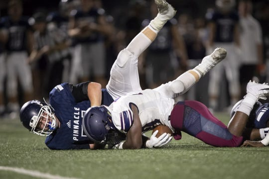 Running back Jalen Young (28) of the Perry Pumas runs the ball against defensive tackle Drew Achor (71) of the Pinnacle Pioneers at Pinnacle High School on Friday, August 17, 2018 in Phoenix, Arizona.