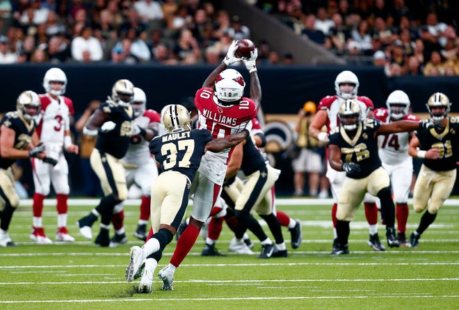 Arizona Cardinals wide receiver Chad Williams (10) pulls in a pass as New Orleans Saints cornerback Arthur Maulet (37) covers in the first half of an NFL preseason football game in New Orleans, Friday, Aug. 17, 2018.