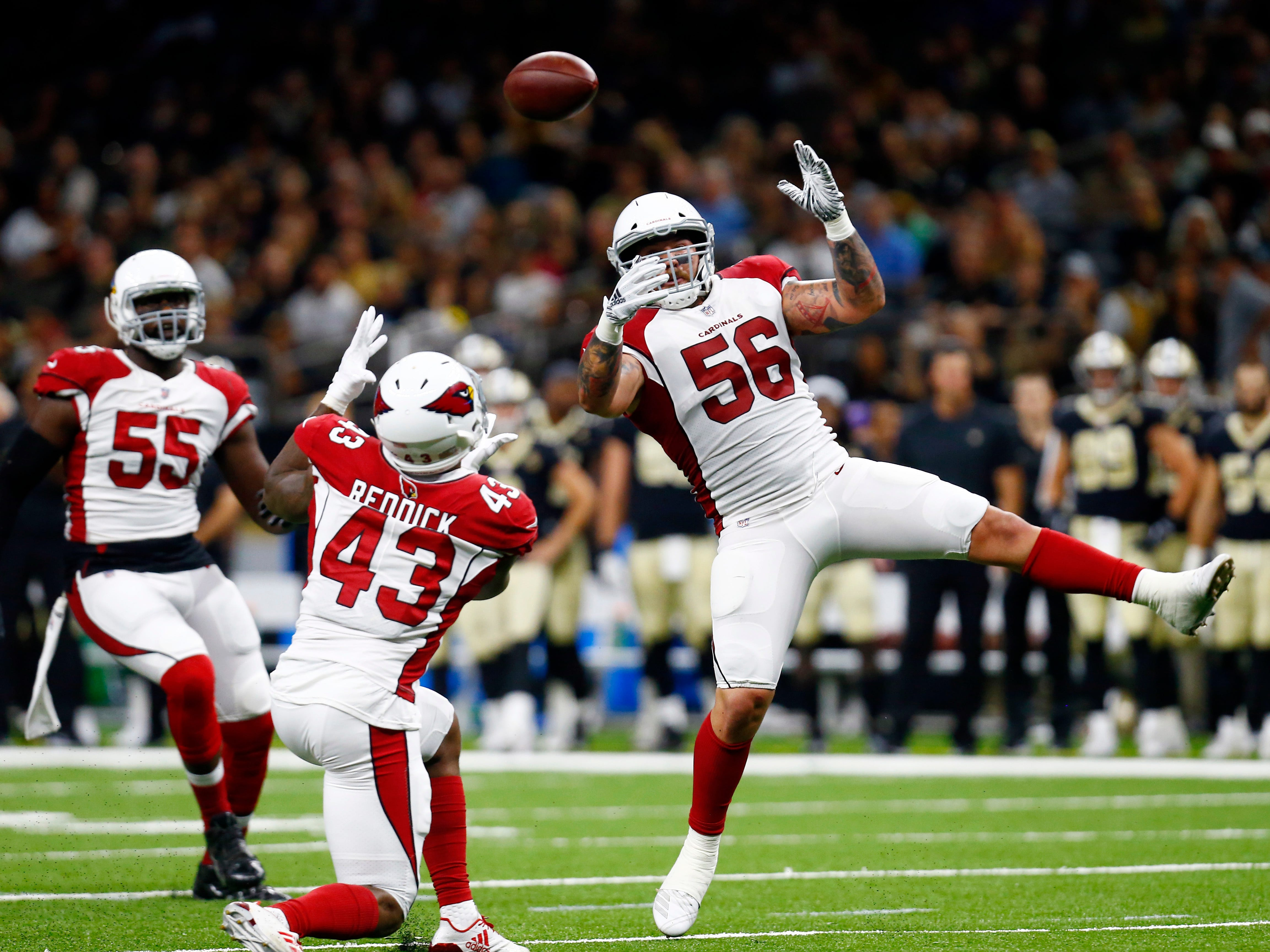 Arizona Cardinals linebacker Haason Reddick (43) intercepts a pass on a deflection by linebacker Demario Davis (56) in the first half of an NFL preseason football game against the New Orleans Saints in New Orleans, Friday, Aug. 17, 2018.