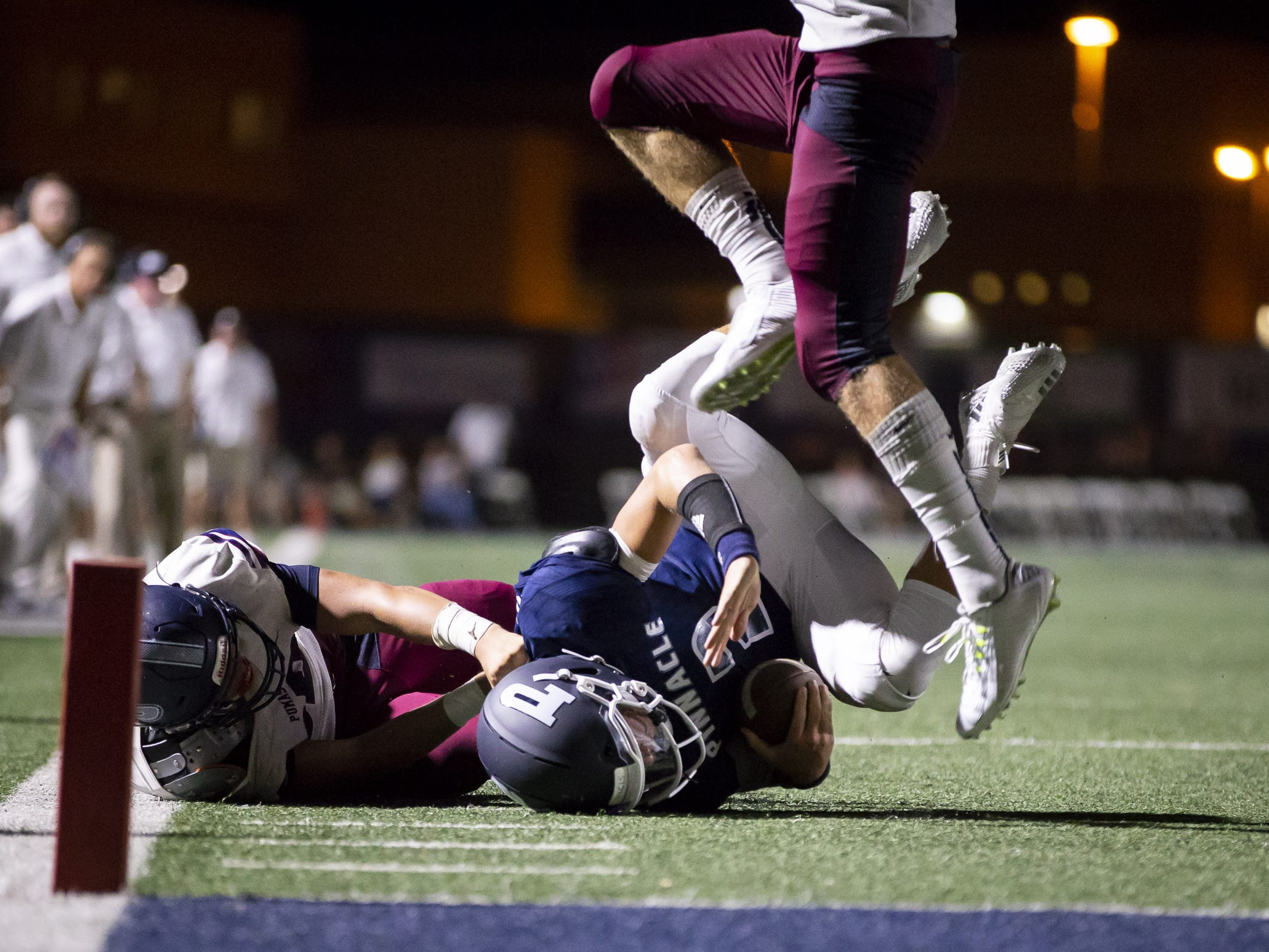 Quarterback Spencer Rattler (2) of the Pinnacle Pioneers is brought down by defensive end Ryan Short (33) of the Perry Pumas at Pinnacle High School on Friday, August 17, 2018 in Phoenix, Arizona.