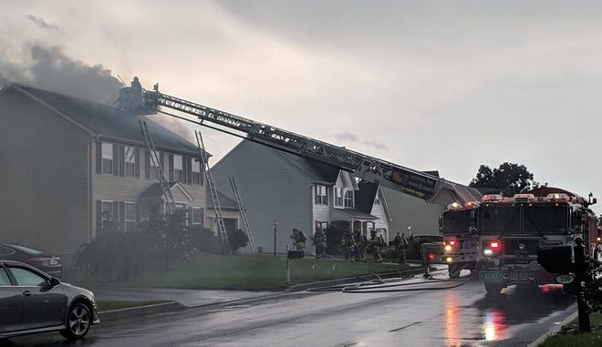 Firefighters battle a blaze caused by a lightning strike on Parliament Drive in Annville on Friday, Aug. 17, 2018. Two firefighters were injured while putting out the fire.