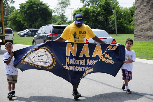 Kevin Watkins, president of the Port Huron branch of the NAACP, leads the parade with Jamarius Waldon and Javani Khammo.