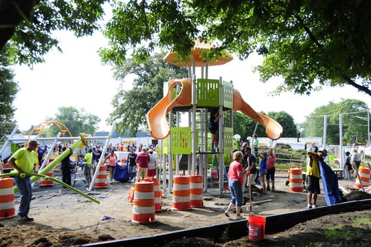 Volunteers build a new playscape at Optimist Park in Port Huron on Saturday, Aug. 18, 2018.