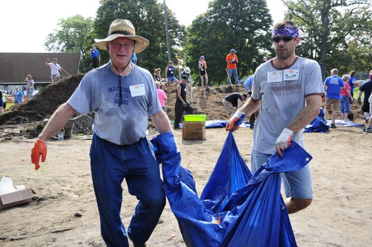 Rich Huegli, left, and Scott Singer carry a load of mulch at the new playscape at Optimist Park in Port Huron on Saturday, Aug. 18, 2018.