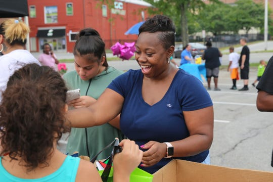 Volunteer Tamoya Norwood hands out school supplies on Saturday at a giveaway in the City of Poughkeepsie put on by the nonprofit Rebuilding Our Children and Community Inc. There were more than 300 backpacks available at the event.