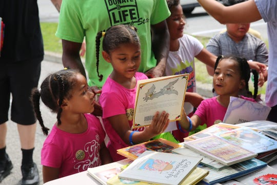 Naomi Miles (left), Rebekah Miles (center) and Hannah Miles (right) look at books on Saturday. Their father recently lost his job and said the event helped him.