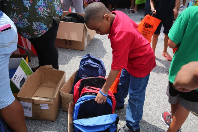 Naithen Daily, 7, rifles through a box of backpacks at the fourth annual giveaway of school supplies put on by the nonprofit Rebuilding Our Children and Community Inc. He also filled a bag with books.