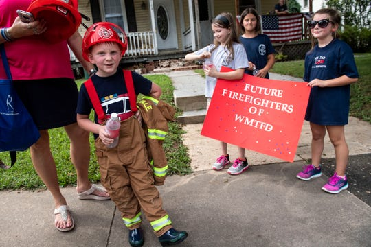 Flynn Ort, 5, of Spring Grove, drinks water after walking in the York County Fireman's Parade, celebrating Alert Fire Company's 100th year, Saturday, August 18, 2018.