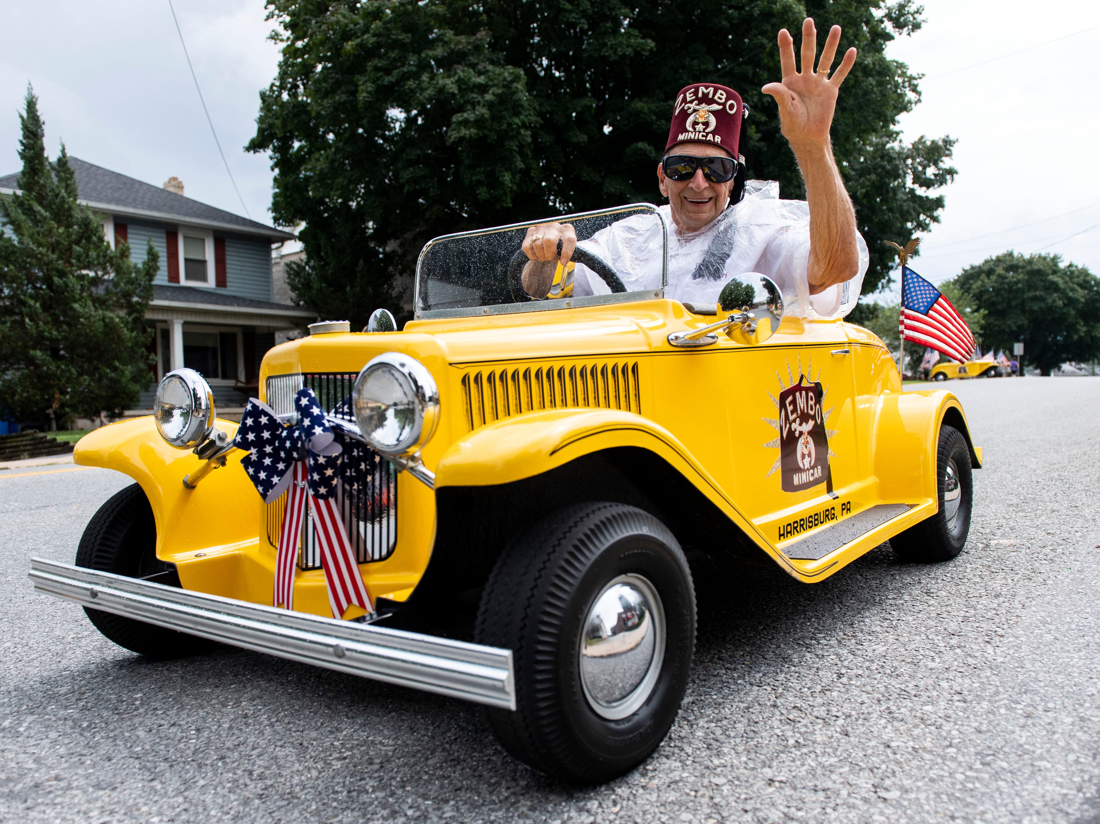A Zembo minicar driver waves while doing a routine during the York County Fireman's Parade, celebrating Alert Fire Company's 100th year, Saturday, August 18, 2018.