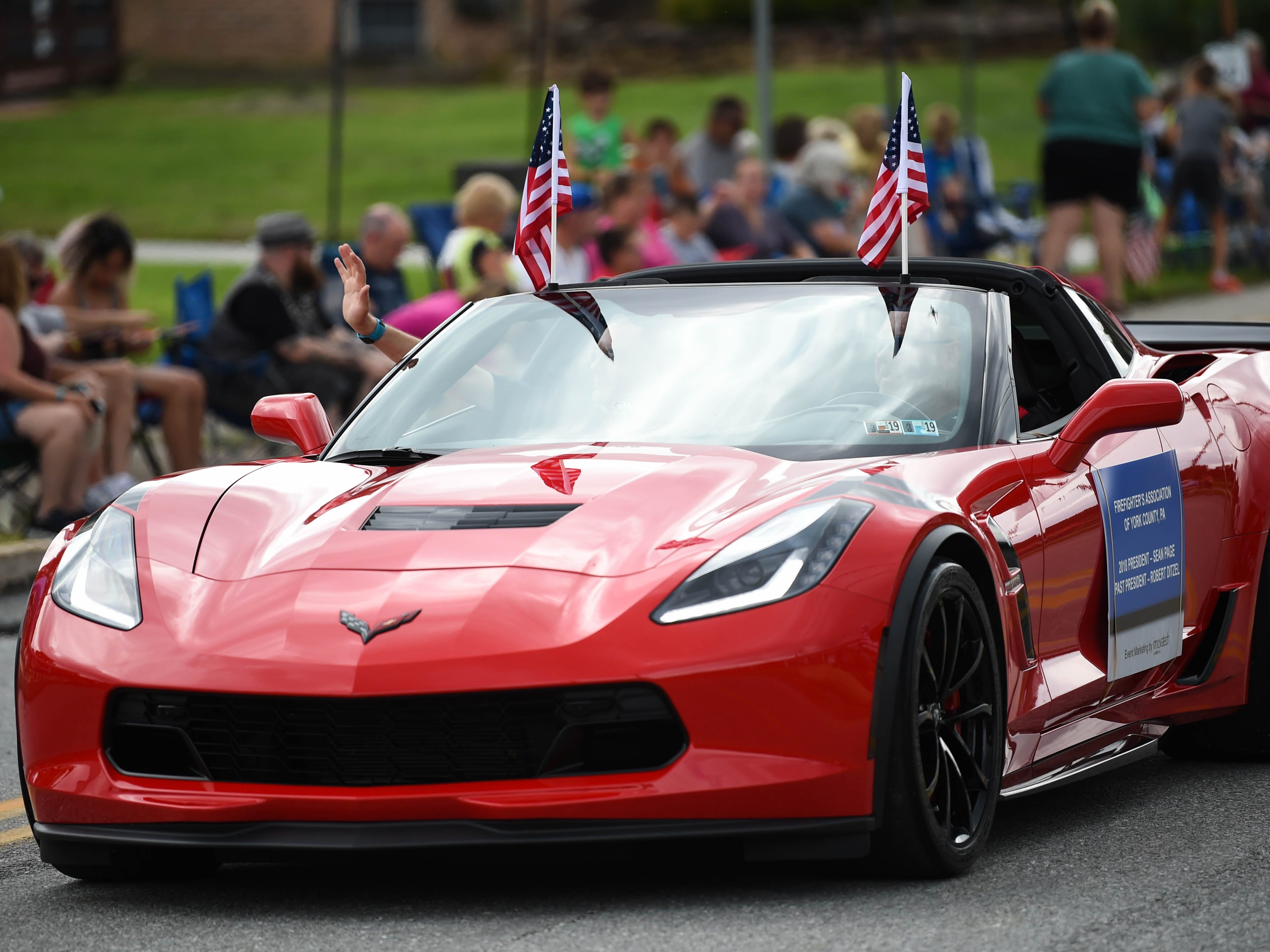 A Corvette passenger greets onlookers during the York County Firemen's Parade, celebrating Alert Fire Company's 100th year, Saturday, August 18, 2018.