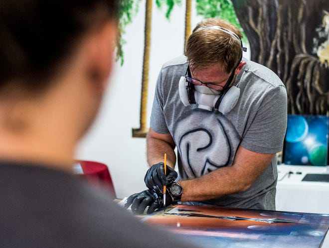 A visitor to Paint the Towne in the Depot District watches as Rick Wenning creates a piece during an art walk event on Friday, Aug. 17, 2018.