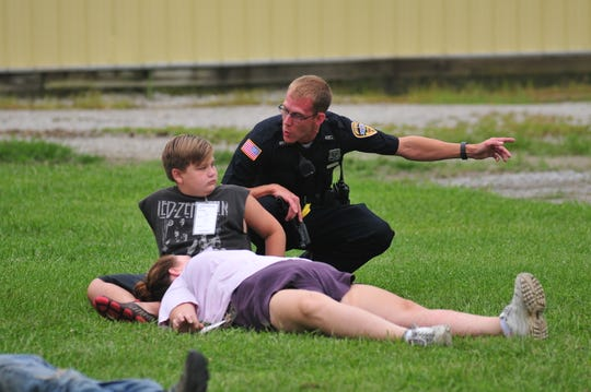 Officer Chris Cooper gives directions to pretend victims during a mass-casualty training exercise Saturday at the Wayne County Fairgrounds.