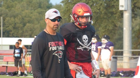 Foothill quarterback Jayden Gordon and an assistant coach watch teams scrimmage. Football teams for Foothill, Shasta and Enterprise High gathered at Foothill on Friday for a three-way scrimmage. The field was split at the 50-yard line, and teams alternated offensive and defensive series.