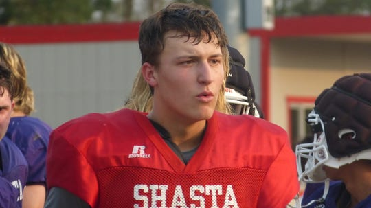 Shasta High quarterback Brian Kilgore talks to a teammate. Football teams for Foothill, Shasta and Enterprise High gathered at Foothill on Friday for a three-way scrimmage. The field was split at the 50-yard line, and teams alternated offensive and defensive series.