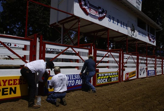 Dave Wilson, from left, Randy Steffen and Bill Smith, Rodeo president, put up a sponsor sign at the St. Paul Rodeo Tuesday 6/29/04.