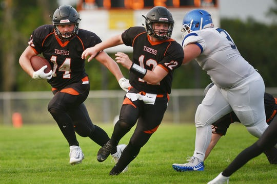 Howard's 	Michael Hofer (14) runs the ball with 	Isaac Feldhaus (12) against Garretson during the game Friday, Aug 17, in Howard.