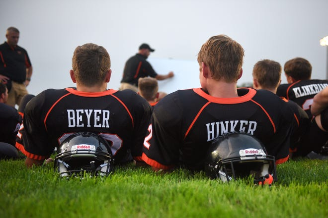 Howard's Ty Beyer, left and Brayden Hinker, right, listen to coaches during half time during the game against  Garretson Friday, Aug 17, in Howard.