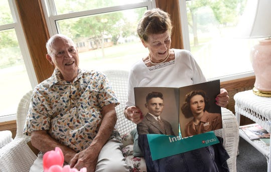 Twins Virgil Egerman and Ginny Egerman Symons display their high school graduation photographs during an interview Saturday, Aug. 18, in St. Cloud.
