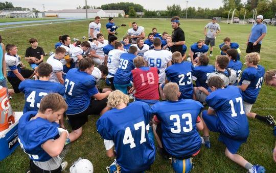 Players gather around head coach John Benson during practice Tuesday, Aug. 14, at Kimball High School.