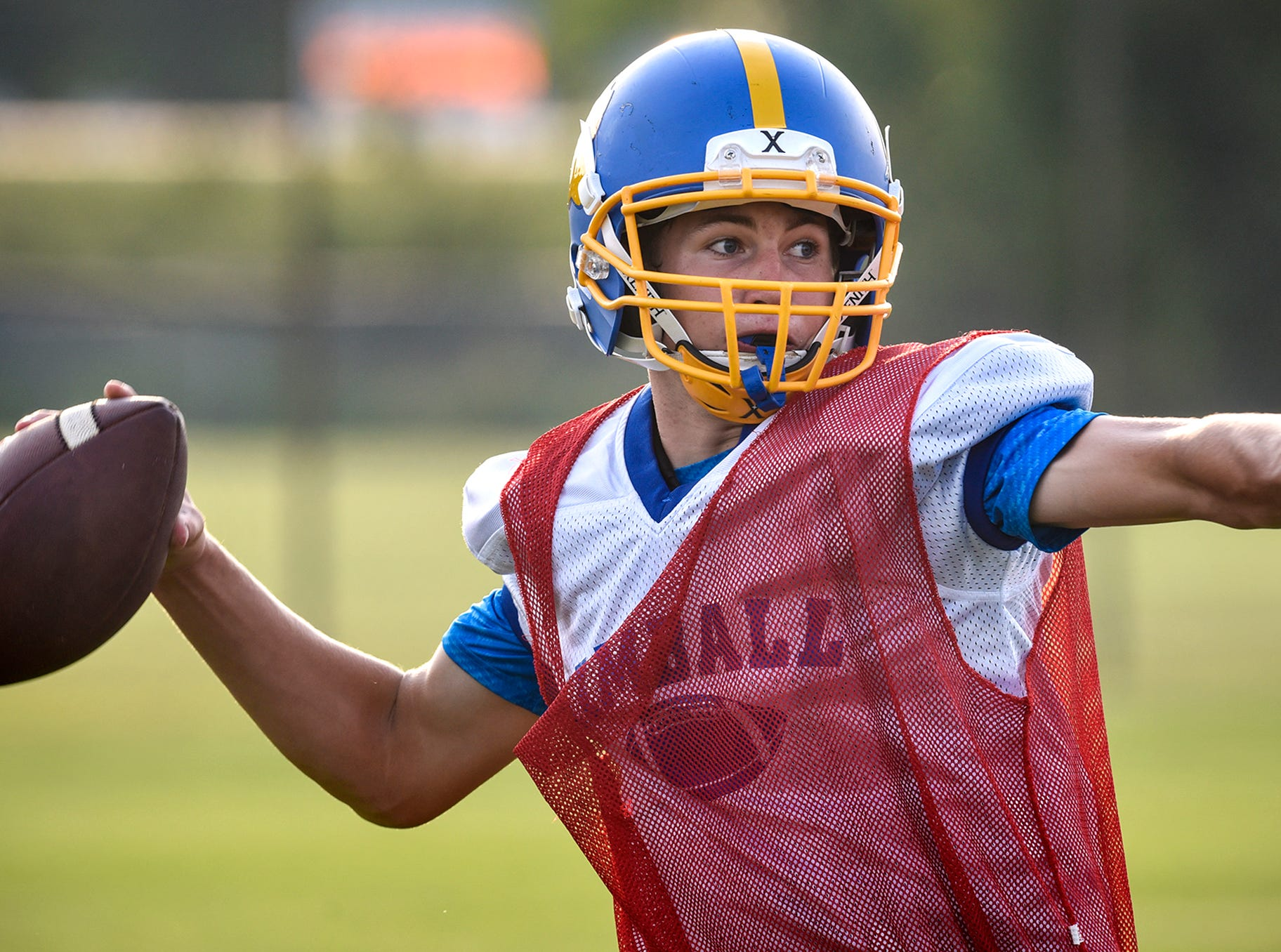Quarterback Tucker Schultz drops back to pass during practice Tuesday, Aug. 14, at Kimball High School.