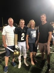 Carson Holyoak stands with his family after scoring the winning touchdown for Snow Canyon on a 100-yard interception in overtime to give the Warriors a 35-29 victory over Taylorsville.