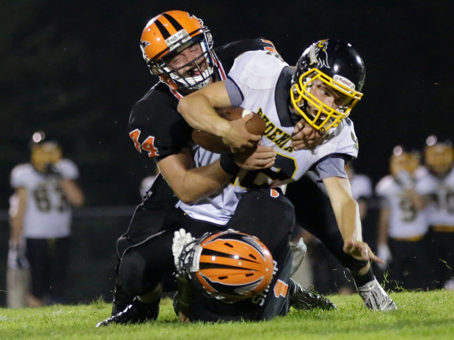 Iola's Kyle Huettner (44) and Alex Sharp (1) tackle Montello's Guenther Hebbe (22) during the first football game of the season, between Iola-Scandinavia and Montello/Princeton/Green Lake at Thunderbird Field in Scandinavia Friday, August 17, 2018.